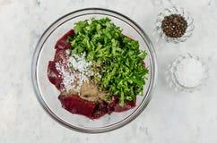Stycken av rå lever i en bunke med löken, koriander och kryddor Fotografering för Bildbyråer