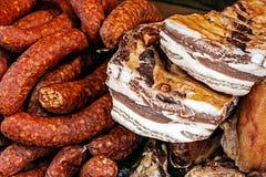 Stycken av rökte grisköttbacon och korvar Royaltyfria Bilder