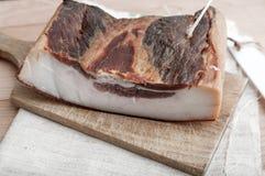 Stycken av rökt grisköttbacon Arkivfoto