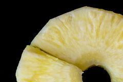Stycken av saftig mogen ananas på en svart bakgrund arkivbilder