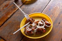 Stycken av stekt kött med stycken av lökar på en plast- platta Arkivfoto