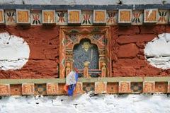 Stycken av torkduken hängdes på en avbildning av Buddha i en buddistisk tempel som placerades i bygden nära Thimphu (Bhutan) Arkivfoton