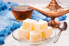 Stycken av turkisk fröjd på en platta och en kopp te Arkivfoton
