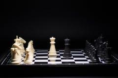 Stycken för ett schack som blir mot svarta schackstycken Arkivfoto