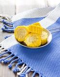 Stycken för majsmajskolv på trätabellen med den marinblåa kökshandduken Royaltyfria Bilder