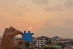 Stycken för maninnehavpussel, solresningbakgrund, teamworkconce royaltyfri fotografi