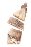 Stycken för salt torsk som isoleras på vit Arkivbild