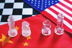 Stycken för schackbrädelek på USA och Kina flaggabakgrund, handlar begrepp för krigspänningsläge arkivbild