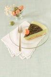 Stycket av den easter kakan med tematcha dekorerade chokladganache- och sötsak-material ägg på den glass plattan Royaltyfria Bilder