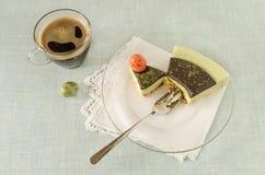 Stycket av den easter kakan med tematcha dekorerade chokladganache- och sötsak-material ägg på den glass plattan Arkivfoton