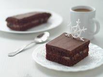Stycket av den hemlagade chokladkakan dekorerade med sockersnöflingan Royaltyfria Bilder