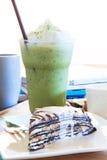 Stycket av den mable kakan med vaniljkräm och kyler grönt te i gla Fotografering för Bildbyråer