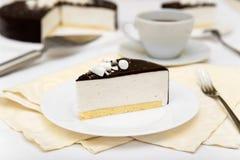 Stycket av kakan med ` s för souffle`-fågeln mjölkar `, kexet, mousse och mörkerchoklad på en vit platta Royaltyfri Foto