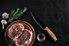 Stycket av nötköttfläskkarrén, med kniven för att klippa och att hugga av kött, kryddor lagade mat - rosmarin, pepprar, salt, vit Royaltyfri Foto