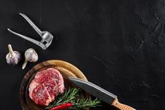 Stycket av nötköttfläskkarrén, med kniven för att klippa och att hugga av kött, kryddor lagade mat - rosmarin, pepprar, salt, vit Royaltyfria Foton