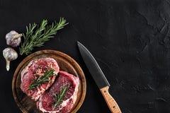 Stycket av nötköttfläskkarrén, med kniven för att klippa och att hugga av kött, kryddor lagade mat - rosmarin, pepprar, salt, vit Royaltyfri Fotografi