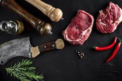 Stycket av nötköttfläskkarrén, med yxan för att klippa och att hugga av kött, kryddor lagade mat - rosmarin, peppar på gammal sva Royaltyfria Bilder