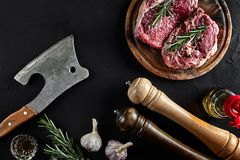 Stycket av nötköttfläskkarrén, med yxan för att klippa och att hugga av kött, kryddor lagade mat - rosmarin, pepprar, salt, vitlö Arkivbild