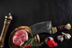 Stycket av nötköttfläskkarrén, med yxan för att klippa och att hugga av kött, kryddor lagade mat - rosmarin, pepprar, salt, vitlö Arkivbilder