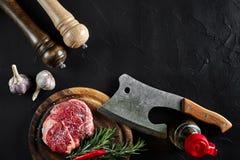 Stycket av nötköttfläskkarrén, med yxan för att klippa och att hugga av kött, kryddor lagade mat - rosmarin, pepprar, salt, vitlö Fotografering för Bildbyråer