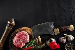 Stycket av nötköttfläskkarrén, med yxan för att klippa och att hugga av kött, kryddor lagade mat - rosmarin, pepprar, salt, vitlö Royaltyfria Foton