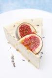 Stycket av ostkaka med honung och lavendel dekorerade med fikonträd arkivfoton