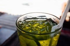 Styckis i gul drink i exponeringsglas Uppfriskande dryck med is i ett exponeringsglas Fotografering för Bildbyråer