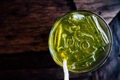 Styckis i gul drink i exponeringsglas Uppfriskande dryck med is i ett exponeringsglas Royaltyfria Bilder
