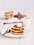 Styckostkaka och en kräm, en sked, häller honung, kaffe, Arkivbilder