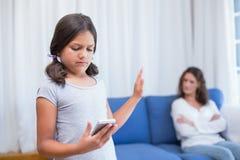 Stygg flicka som använder smartphonen Arkivbild