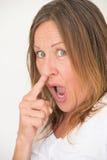 Styggt finger för kvinnanäsplockning Arkivbild