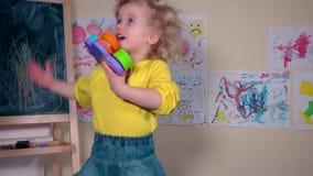Styggt lyckligt barn som hemma kastar hennes leksaker arkivfilmer