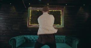 Stylów wolnych mężczyzna tanczy w zadziwiającym projekta wnętrzu z światłami i aksamitną kanapą w środku zbiory