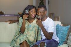 Styl życia domowy portret młoda romantycznego i szczęśliwego czarnego Afro Amerykańska para w miłości pije wino filiżankę przy ży zdjęcia stock