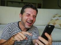 Styl życia domowy portret młody szczęśliwy mężczyzna śmia się jak szalony używa telefonu komórkowego dopatrywanie coś śmiesznego  obraz stock