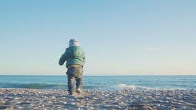 Styl życia dziecko Chłopiec biega morze przy zmierzchem Wakacyjny pojęcie swobodny ruch zbiory