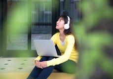 Styl życia dziewczyna cieszy się słuchającego muzyki i sztuki laptop w natura parku Obrazy Royalty Free