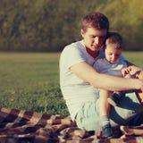 Styl życia fotografii uroczy ojciec i syn wpólnie odpoczywa outdoors zdjęcia royalty free