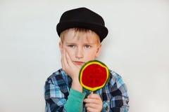 Styl życia i ludzie pojęć Urocza chłopiec trzyma lizaka w w nakrętce, sprawdzać koszula z niebieskimi oczami i zdjęcia stock