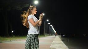 Styl życia kobieta z telefonem w jej ręce w nocy mieście komunikuje z przyjaciółmi na ogólnospołecznych sieciach zbiory