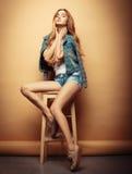 Styl życia, moda i ludzie pojęć: Pełny ciało portret moda modela obsiadanie na drewnianym krześle w studiu Obraz Stock