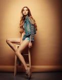 Styl życia, moda i ludzie pojęć: Pełny ciało portret moda modela obsiadanie na drewnianym krześle w studiu Zdjęcia Stock