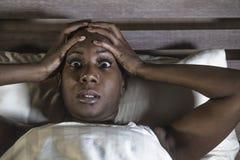 Styl życia nocy portret potomstwa okaleczający i stresująca się czarna afro Amerykańska kobieta deprymująca na łóżka spęczeniu ni fotografia royalty free