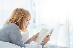 Styl życia szczęśliwa młoda Azjatycka kobieta cieszy się kłamać na łóżkowej czytelniczej książki przyjemności w przypadkowej odzi Zdjęcia Royalty Free