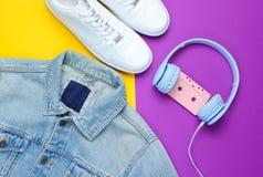styl retro 80s Popkultura minimalista Drelichowa kurtka, hełmofony z audio kasetą, biali sneakers obraz stock
