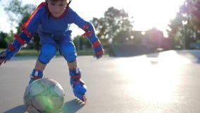 Styl wolny, aktywny dzieciak w kolanowych ochraniaczach bawić się na rolownikach przy dziecka boiskiem na na wolnym powietrzu zbiory wideo