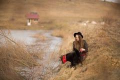 Styl ?ycia portret m?oda kobieta w czarnym kapeluszu z jej psem, odpoczywa jeziorem na ?adnym i ciep?ym jesie? dniu fotografia royalty free