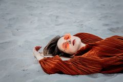 Style adult woman in sunglasses and burgundy color blouse. Lying down on on a sand, beach. Above ivew royalty free stock images