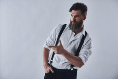 Stylish bearded man. Style. Bearded man in shirt with suspenders is pointing to the e, on a light background stock image