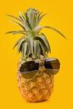 Style de port de hippie en verre d'ananas à la mode d'été sur le jaune Photographie stock